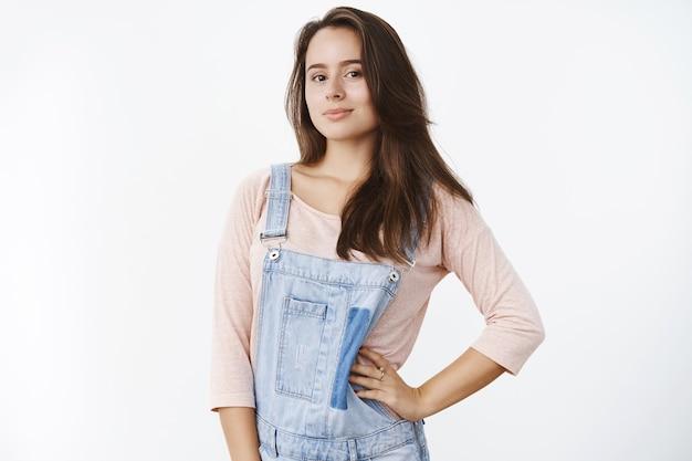 Portret van brutale en stijlvolle knappe vrouwelijke brunette met lang natuurlijk haar in denim overall poseren, hand in de taille en glimlachend zelfverzekerd en zelfverzekerd aan de voorkant over grijze muur.