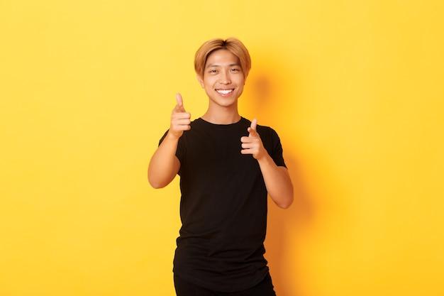 Portret van brutale glimlachende aziatische kerel, die tevreden kijkt en vingers richt, iets prijst of een compliment maakt.