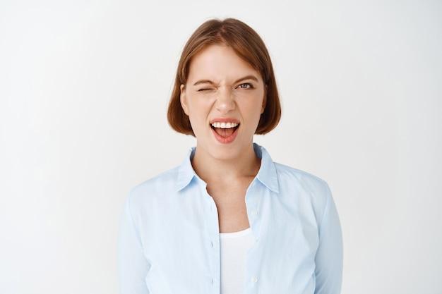 Portret van brutale jonge vrouw die knipoogt en tong toont, plezier heeft. mooi vrouwelijk model ziet er expressief en brutaal uit, witte muur