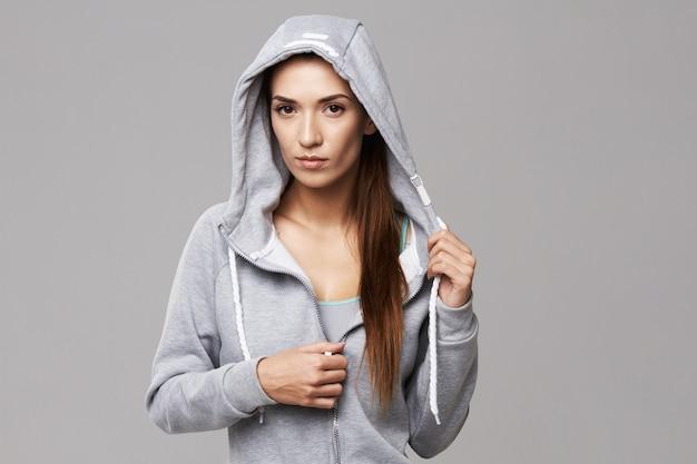 Portret van brute atletische vrouw in kap en sportkleding op wit.