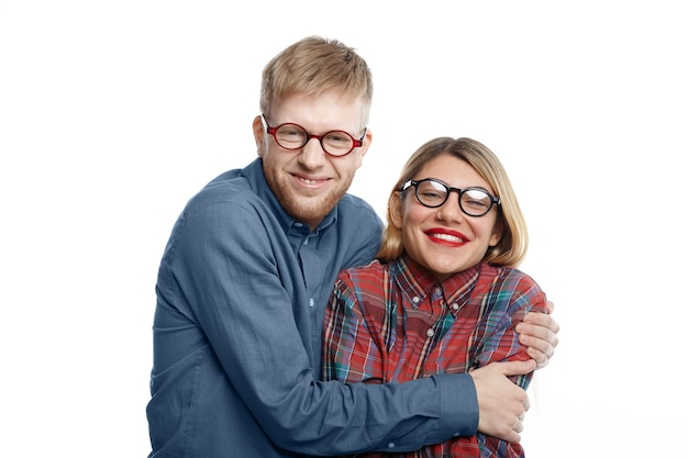 Portret van buitengewone komische jonge kaukasische paar in excentrieke kleding en brillen plezier: geeky man met stoppels knuffelen strak zijn gelukkig aantrekkelijke vriendin met rode lippen en blond haar