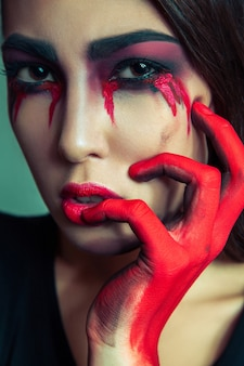 Portret van buitenissig monster met puinhoop vuile gekleurde make-up op haar gezicht. huilende vrouw met rode bloedige tranen en hand. halloween-concept op groene achtergrond. studio opname, donkerbruine ogen.