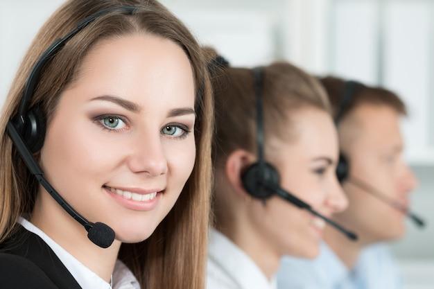 Portret van callcentermedewerker begeleid door haar team. glimlachende klantondersteuningsoperator op het werk. hulp en ondersteuning concept
