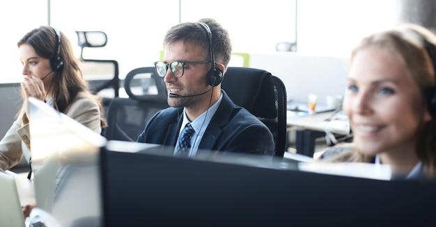 Portret van callcentermedewerker vergezeld door zijn team. glimlachende klantenondersteuningsoperator op het werk.