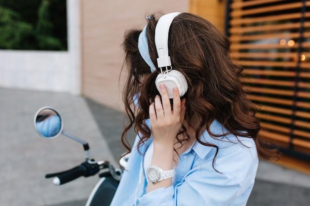 Portret van charmant meisje met glanzend krullend donkerbruin haar, genietend van favoriete muziek in grote witte koptelefoon op bromfiets