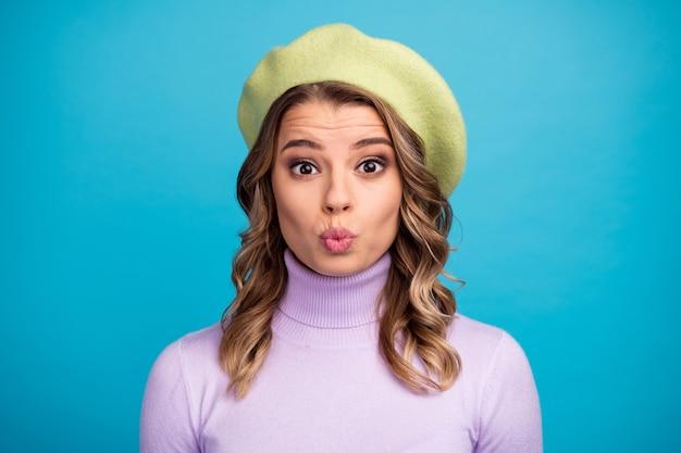 Portret van charmant mooi meisje verzendt luchtkus op blauwe muur