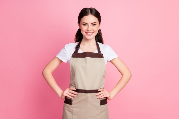 Portret van charmant tevreden meisje in uniforme winkelmanager handen heupen