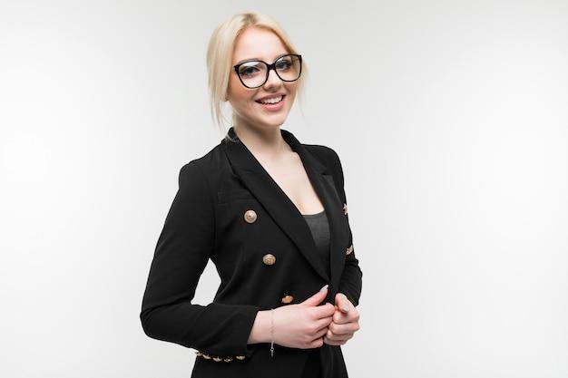Portret van charmante blonde in zwart kostuum die in glazen bezit