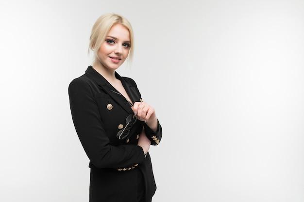 Portret van charmante blonde in zwart kostuum die met een bril op de achtergrond