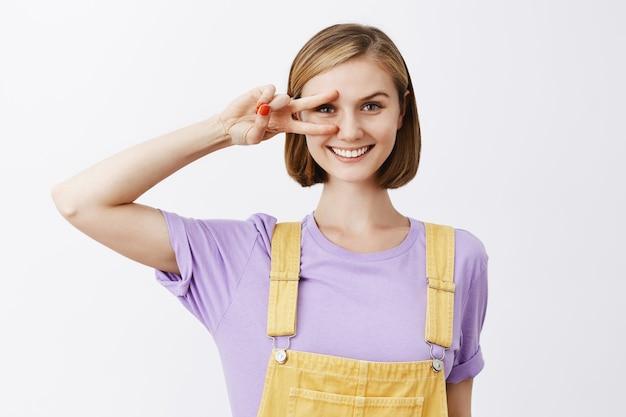 Portret van charmante blonde met kort kapsel, overwinningsteken over oog tonen en vreugdevol glimlachen