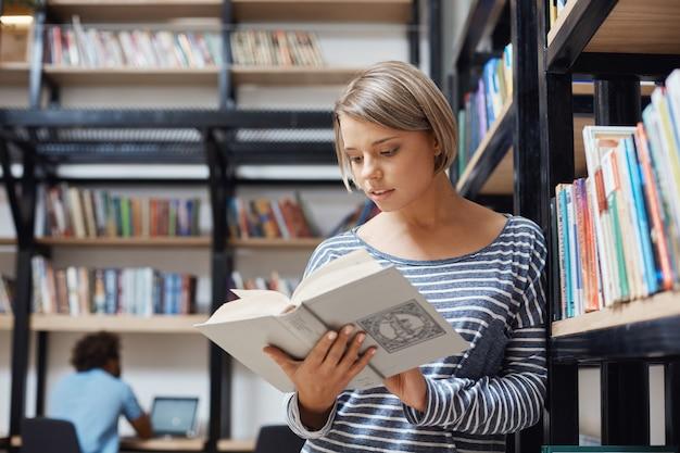 Portret van charmante blonde student meisje met kort haar in casual kleding staande in de buurt van plank in bibliotheek, leesboek, op zoek via informatie over economische systemen.
