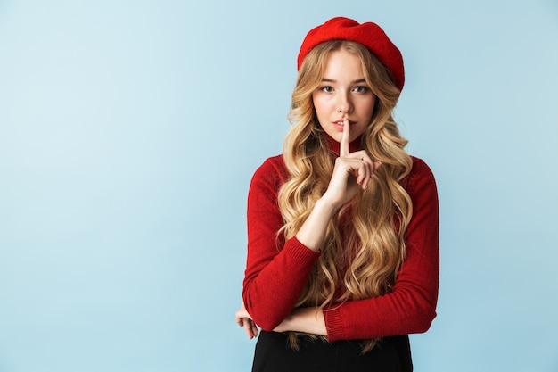 Portret van charmante blonde vrouwen20s die de vinger van de rode baretholding bij mond dragen terwijl status, geïsoleerd