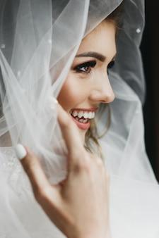Portret van charmante bruid gehuld in een sluier