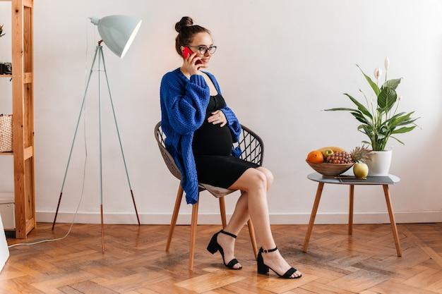 Portret van charmante dame in zwarte jurk en blauw vest praten over de telefoon en zittend op een houten stoel. zwangere vrouw in oogglazen raakt buik.