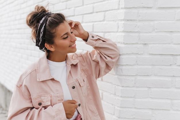 Portret van charmante donkerharige vrouw in roze jasje leunde op lichte bakstenen muur