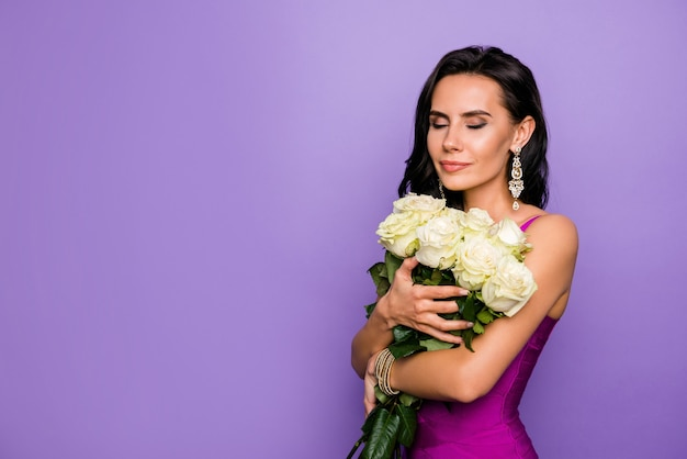 Portret van charmante dromerige dame met ruikende verse rozen close-up