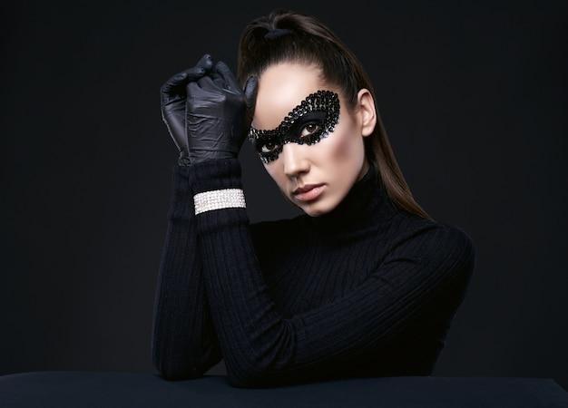 Portret van charmante elegante brunette vrouw in coltrui trui en pailletten masker poseren op zwart in de studio