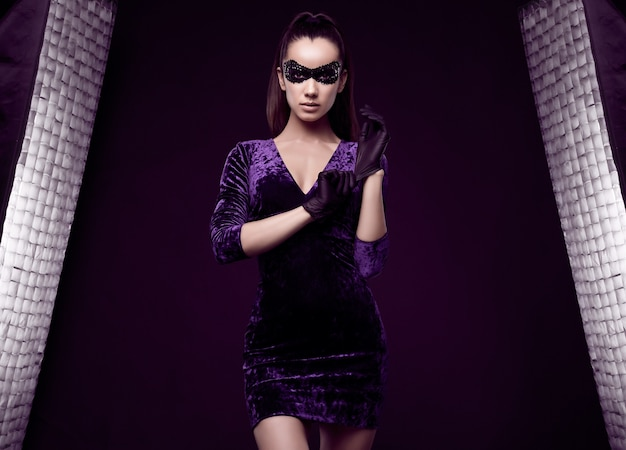 Portret van charmante elegante brunette vrouw in prachtige paarse jurk en pailletten masker