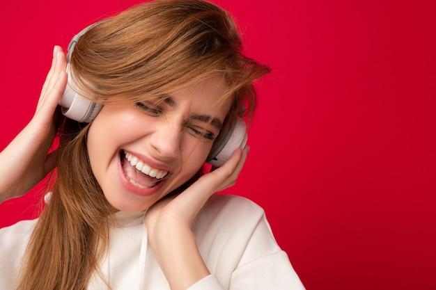 Portret van charmante emotionele positieve jonge blonde vrouw die witte hoodie draagt die over kleurrijke muur wordt geïsoleerd die witte draadloze bluetoothhoofdtelefoons draagt die naar goede muziek luisteren en pret hebben.