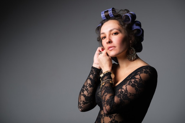 Portret van charmante en jonge mooie vrouw in haarkrulspelden die zich oorringen in transparant zwart overhemd kleden