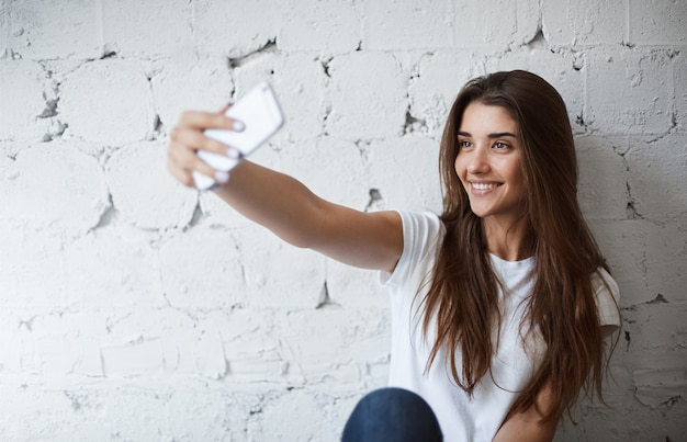 Portret van charmante europese vrouwelijke model, selfie maken op smartphone in de buurt van witte bakstenen muur, vrolijk glimlachend. trendy blogger maakt een foto om deze op haar blog te plaatsen. ze heeft veel fans.