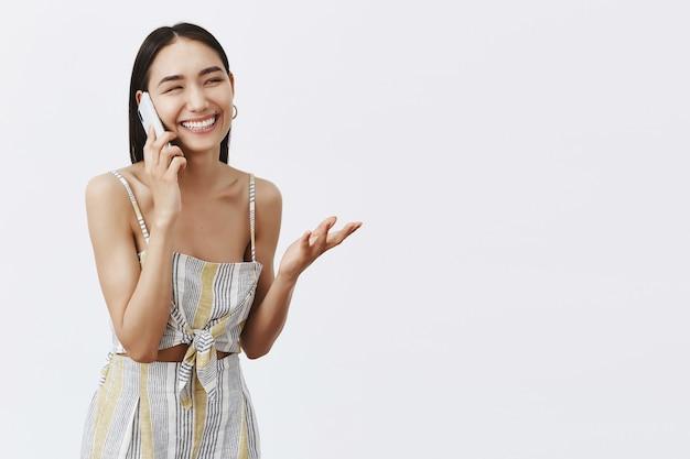 Portret van charmante gelukkig elegante vrouw in bijpassende outfit, gebaren met de hand tijdens het vreugdevol praten aan de telefoon, smartphone vasthouden, lachen en glimlachen