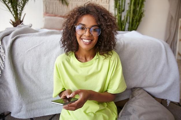 Portret van charmante gelukkig jonge vrouw met donkere huid en bruine krullen, vrolijk op zoek met smartphone in handen, poseren over interieur
