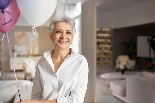 Portret van charmante gelukkig volwassen vrouw draagt formele shirt met plezier op haar pensioen feestje, poseren in kantoor interieur met helium ballonnen