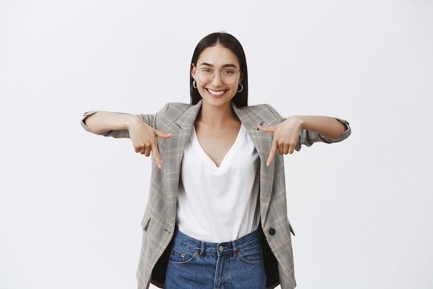 Portret van charmante gelukkige jonge ondernemer in brillen en stijlvol jasje, naar beneden wijzend met opgeheven handen en glimlachend met zelfverzekerde tevreden uitdrukking