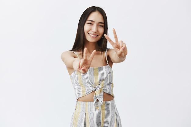 Portret van charmante gelukkige vrouw die handen naar met overwinningstekens trekt en vreugdevol glimlacht, die zich voordeed over grijze muur