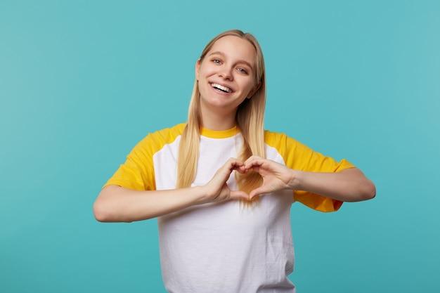 Portret van charmante jonge blonde dame met lang haar die hart met opgeheven handen vormen en gelukkig glimlachen bij camera, die zich tegen blauwe achtergrond bevindt