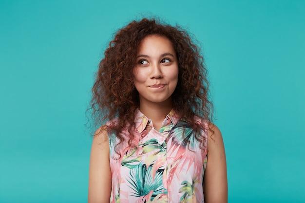 Portret van charmante jonge krullende brunette vrouw met natuurlijke make-up haar lippen bijten terwijl ze positief opzij kijken, geïsoleerd op blauw met handen naar beneden