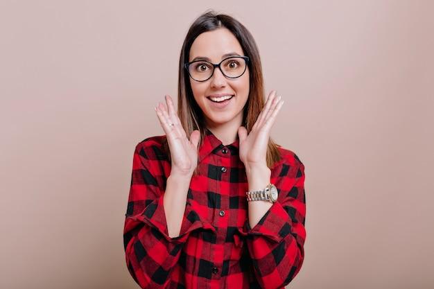 Portret van charmante jonge vrouw gekleed overhemd en bril met verbaasde emoties en opgewekte handen op geïsoleerde muur