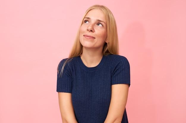 Portret van charmante jonge vrouw met lang blond haar poseren geïsoleerd gekleed in donkerblauw t-shirt opzoeken met dromerige glimlach, na te denken over de toekomst