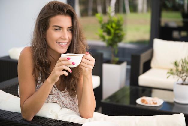Portret van charmante jonge vrouw op terras koffie drinken