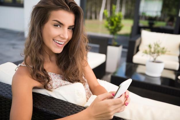 Portret van charmante jonge vrouw op terras met smartphone