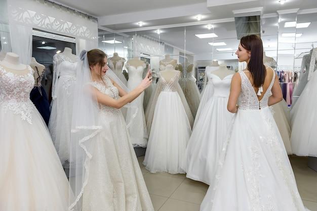 Portret van charmante jonge vrouwen die witte jurken dragen in een bruidssalon