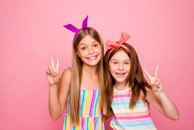 Portret van charmante kinderen die v-tekens maken die lichte kledingsrok dragen die over roze achtergrond wordt geïsoleerd