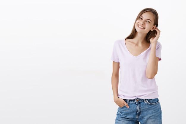 Portret van charmante, onbezorgde, vriendelijk ogende europese vrouw die haarstreng achter het oor flikkert en glimlachend lachend flirterig poseren tegen grijze muur