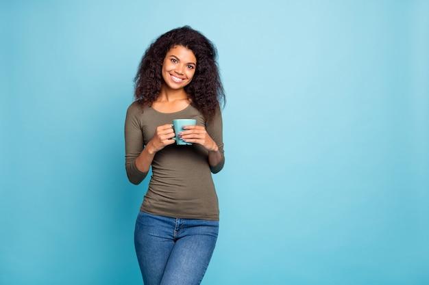 Portret van charmante positieve afro-amerikaanse meisje houdt beker mok met cacao koffie dragen stijlvolle trui denim jeans geïsoleerd over blauwe kleur muur