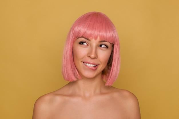 Portret van charmante positieve jongedame met roze trendy bob kapsel dromerig opzij kijken en haar onderlip bijten, haar blauwe ogen loensen terwijl poseren op mosterd achtergrond