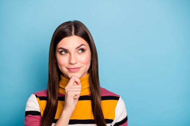 Portret van charmante positieve meisje aanraking handen kin look copyspace denk gedachten over haar prachtige weekends dragen kleurrijke trui geïsoleerd over blauwe kleur muur