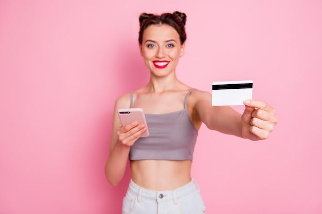 Portret van charmante positieve meisje gebruik smartphone online winkelen gebruiker betalen aankoop met creditcard adviseren zomer dragen grijze witte kleding geïsoleerd over roze kleur