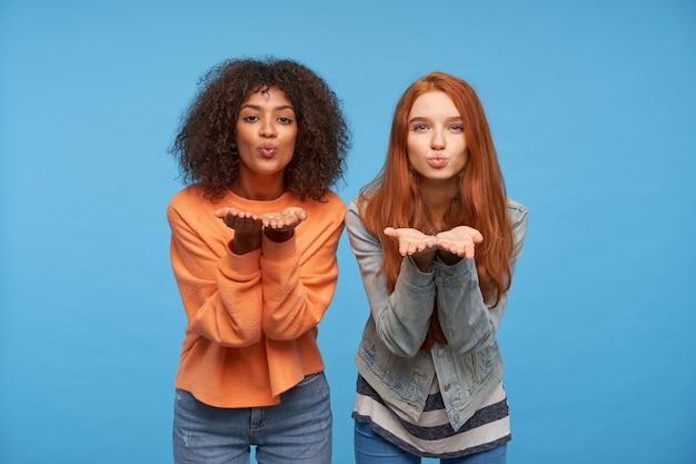 Portret van charmante, positieve, mooie jonge vrouwen die hun handpalmen opheffen terwijl ze over de blauwe muur poseren, hun lippen vouwen en een luchtkus blazen