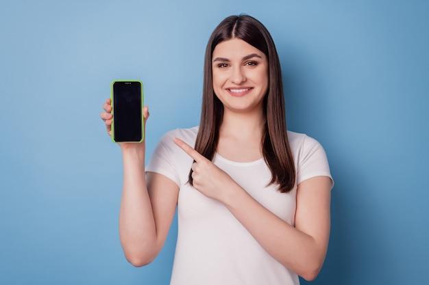 Portret van charmante promotordame houdt smartphone direct vinger-touchscreen vast en toont lege ruimte op blauwe achtergrond