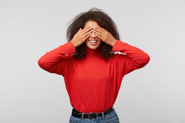 Portret van charmante speelse vrouw met afrokapsel dat ogen bedekt met handpalmen en breed glimlacht van vreugde