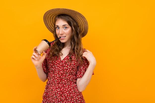 Portret van charmante stijlvolle lachende meisje in een hoed met een papieren beker op geel