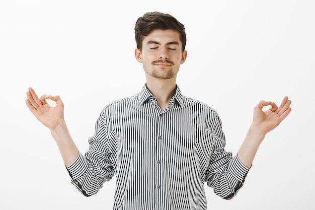 Portret van charmante tevreden blanke man met ontspannen uitdrukking, gespreide handen in zen gebaar, staande met gesloten ogen en tevreden kalme glimlach, mediteren of yoga beoefenen over grijze muur