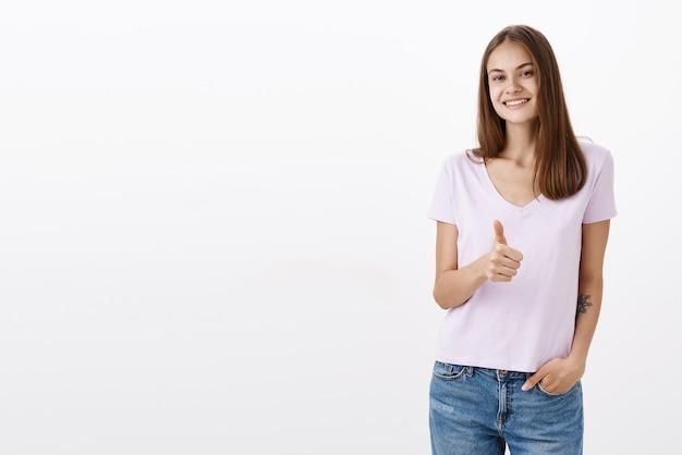 Portret van charmante, vriendelijk ogende zelfverzekerde en gelukkige vrouw met bruin haar en tatoeage hand in de zak terloops glimlachend verzekerd en duim opdagen