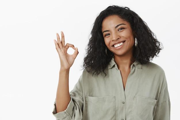 Portret van charmante vriendelijke en beleefde gelukkige afro-amerikaanse volwassen vrouw in blouse kantelend hoofd en glimlachend in grote lijnen ok tonen